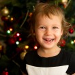 Portrait of little girl in front of Christmas tree — Stock Photo #7786832