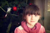 Portrait of little girl in front of Christmas tree — Stock Photo