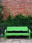 Den gröna bänk och ranka växten på röda väggen — Stockfoto