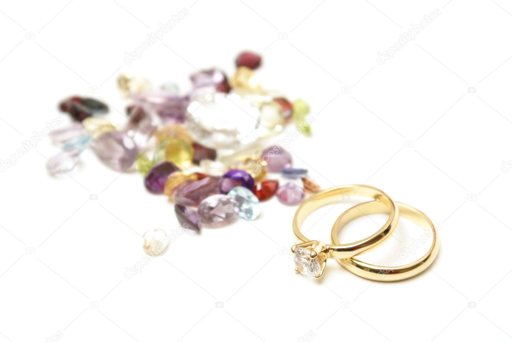 A pair of gold rings with multiple gemstones blurred in the background to accentuate a jewelers delight in stone work.  Stock Photo #6946088