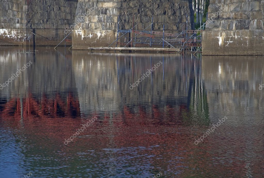 River with ripples and bridge with scaffolding in a urban scene  Stock Photo #6809070