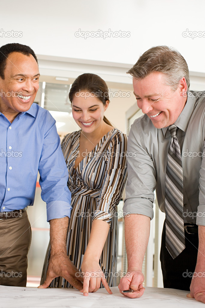 Colleagues looking at plans and smiling — Stock Photo #7029946