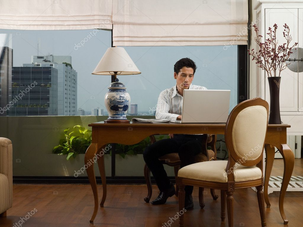 Young man at desk using laptop — Stock Photo #7034084