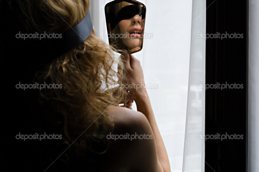 Blindfolded woman with a hand mirror  Stock Photo #7035315