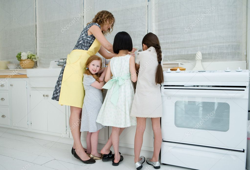 Girls helping woman cook — Stock Photo #7036835