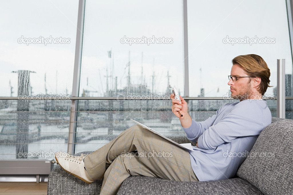 Man on sofa with cellphone  Stock Photo #7037816