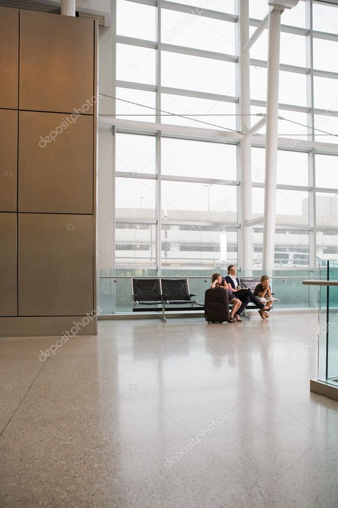 A mother and her children waiting in an airport — Stock Photo #7043082