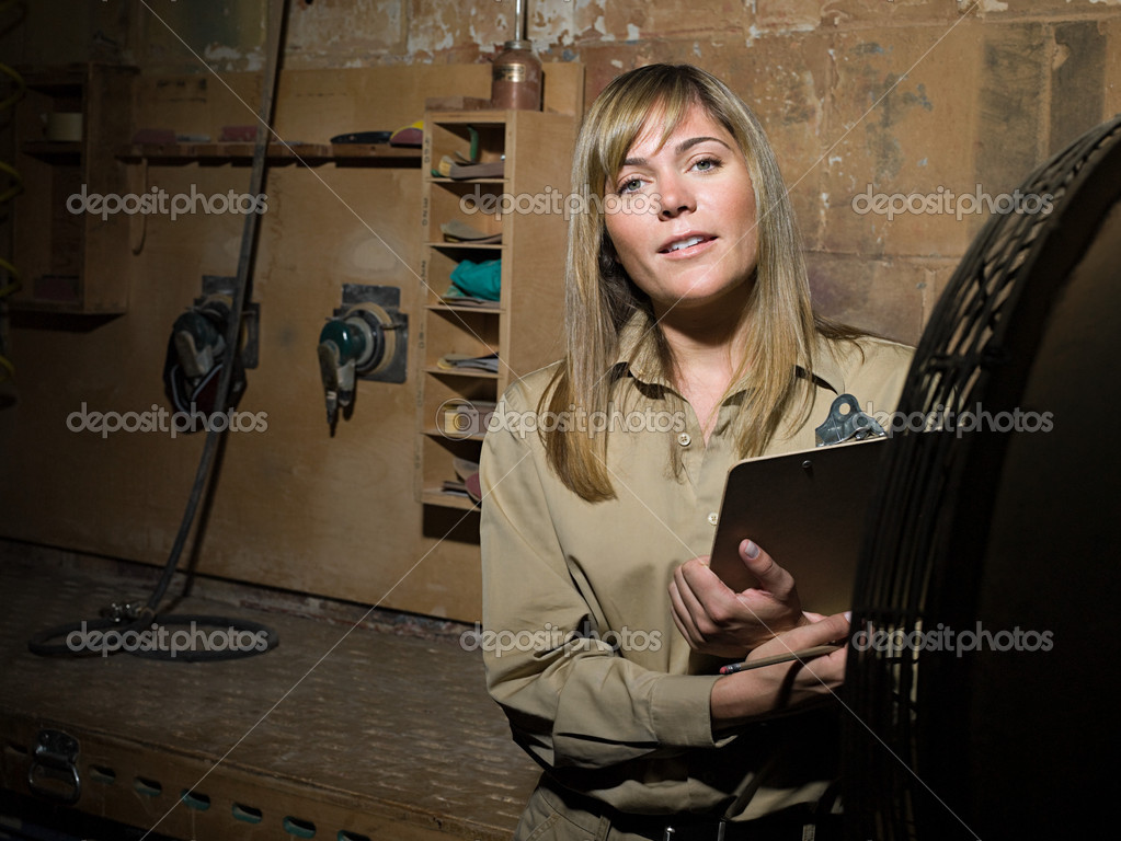 Woman with a clipboard in workshop — Stock Photo #7044245