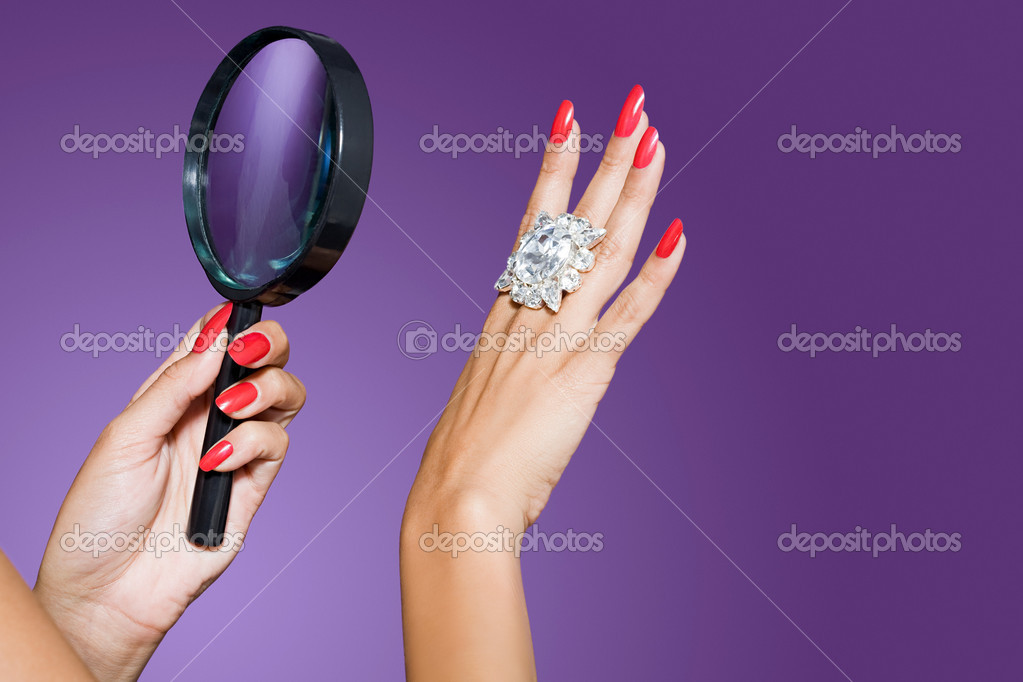 Woman looking at diamond with magnifying glass — Stock fotografie #7045136