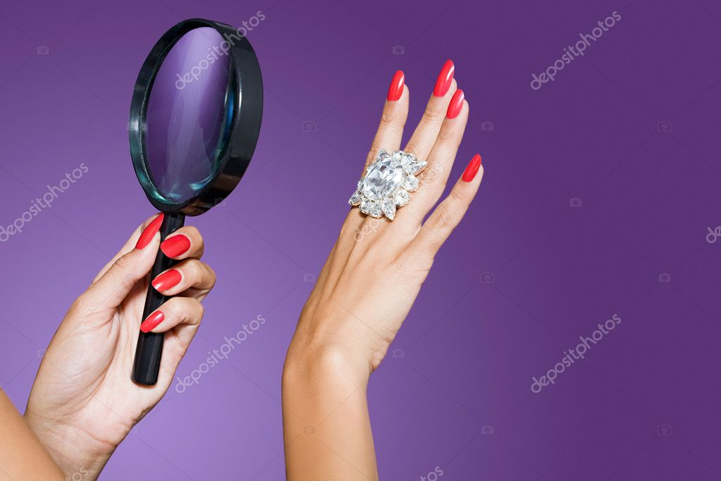 Woman looking at diamond with magnifying glass  Foto de Stock   #7045136