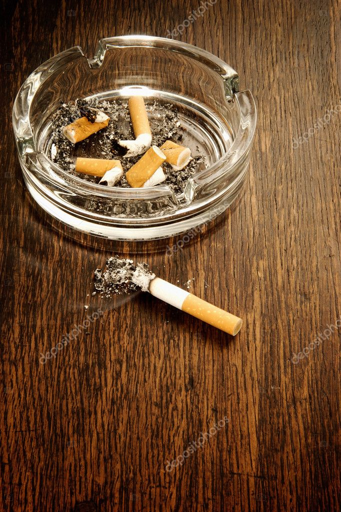 Burning cigarette lying on wooden surface — Stock Photo #7051401