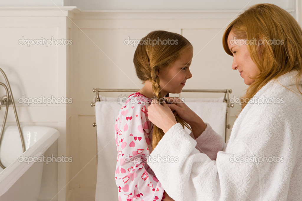 Mother plaiting daughter's hair — Stock Photo #7055222