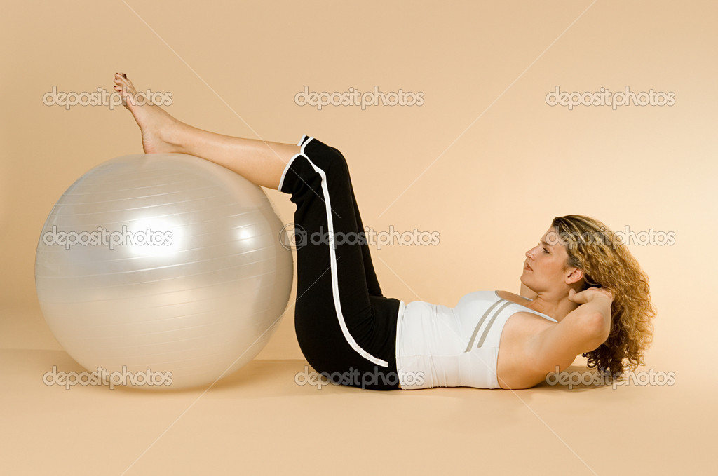 Woman doing sit-ups with exercise ball  Stock Photo #7059971