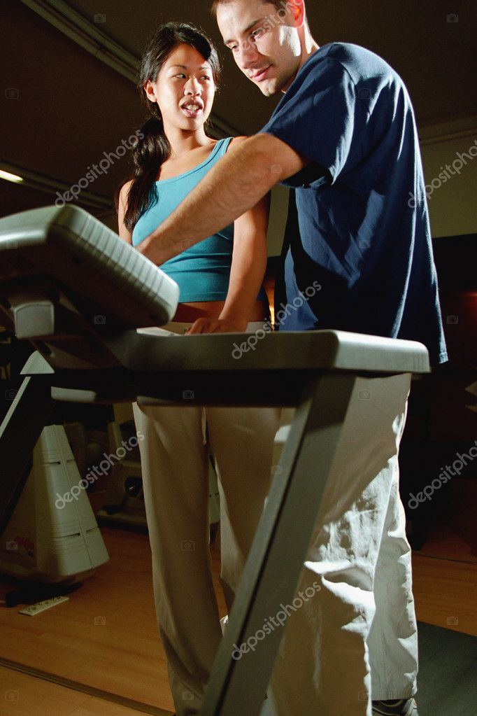 Fitness instructor adjusting gym equipment — Stock Photo #7066309