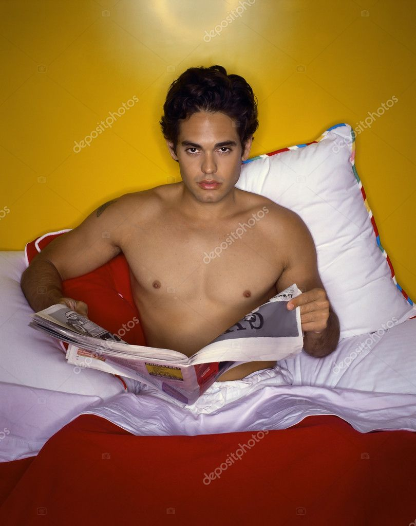 Man reading newspaper in bed  Stock Photo #7067107