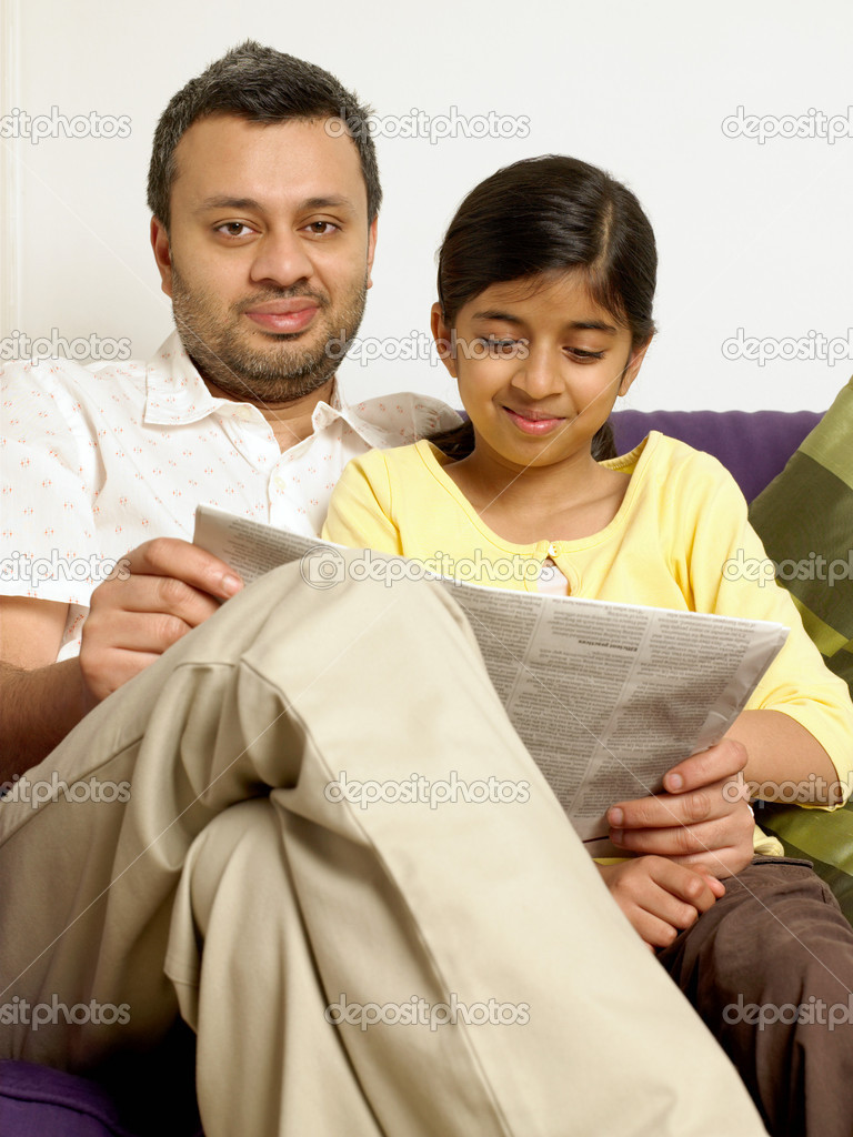 Father and daughter reading a newspaper — Stock Photo #7071348