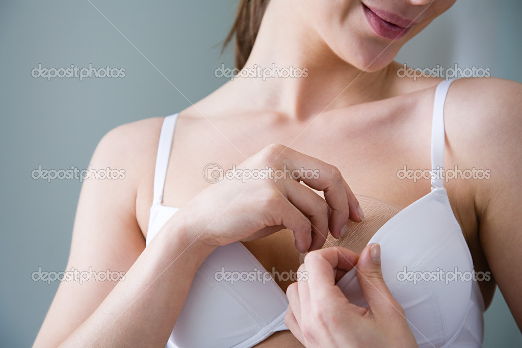 Woman putting bra enhancer into bra  Stock Photo #7076130