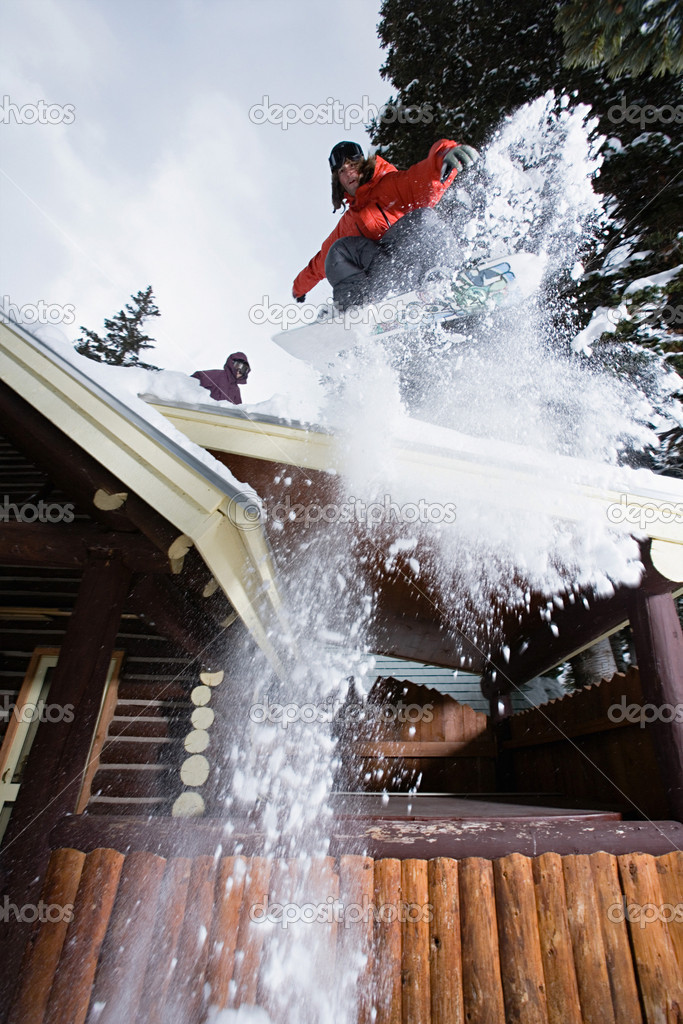 Man snowboarding off chalet roof — Stock Photo #7076775