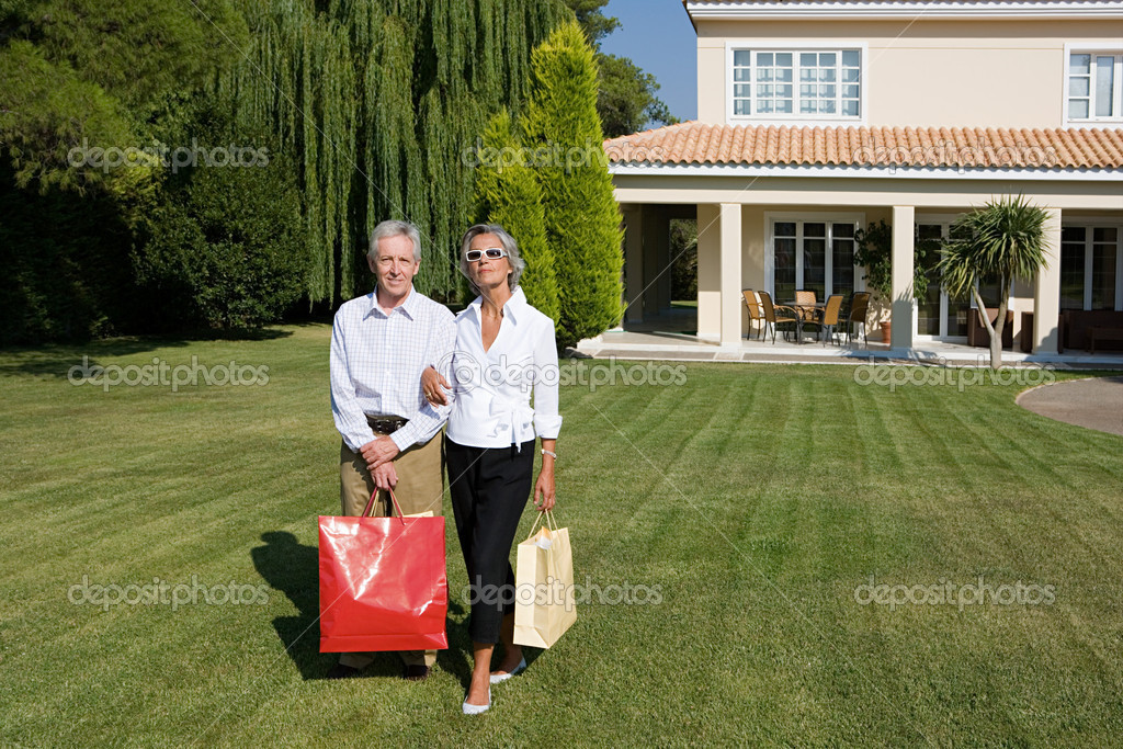 Couple stood outside of villa holding shopping bags — Stock Photo #7078728