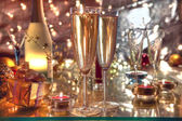 Champagne in glasses,candle lights and gifts. — Stock Photo