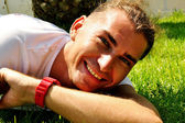 Smiling young man on the grass — Stock Photo