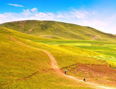 Landscape photo of pepole walking along a road in plain and hill — Stock Photo