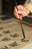 An old man practising calligraphy using a brush pen — Stock Photo