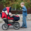 Stock Photo: Brother rolls younger sister in pram.