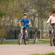 Children go for a drive on bicycles on park. — Stock Photo