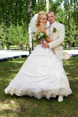 Beautiful bride and groom is walking in the park. — Stock Photo
