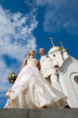 Newlyweds in front of church. — Stock Photo