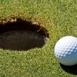 Golf ball next to a hole — Stock Photo