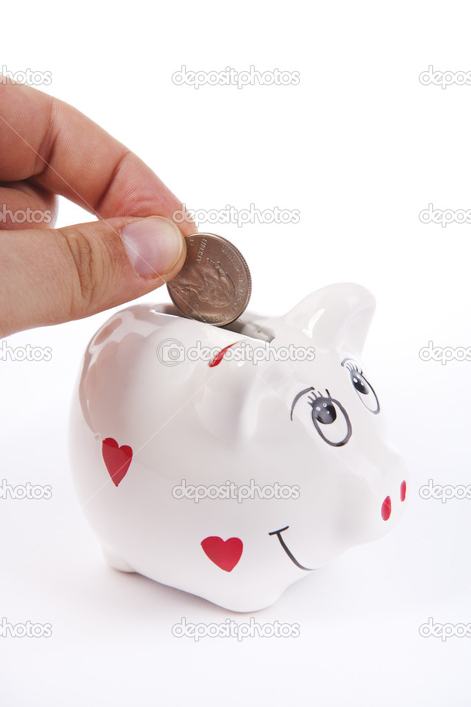 Hand inserting a coin in a piggy bank against a white background  Stock Photo #6954548