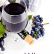 Red wine in glass with grapes — Stock Photo