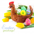 Easter eggs in basket with yellow tulip flowers - Stock Photo