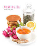 Tea in cup with biscuits and bouquet roses — Stock Photo