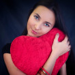 Woman with heart shaped cushion — Stock Photo