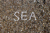 Sea inscription on a beach — Stock Photo