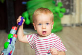 Baby with toy gun — Stock Photo