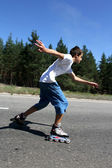 Roller-skating young boy on the road — Stock Photo