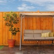 Outdoor Swing Chair in Front of Wooden Cedar Fence - Stock Photo