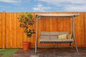 Outdoor Swing Chair in Front of Wooden Cedar Fence — Stock Photo