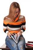 Young student sitting on the desk and leafs book — Stock Photo