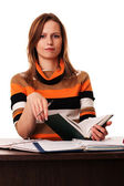 Young woman holding book and pen sitting at the desk — Foto Stock