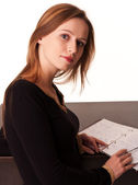 Pretty young girl sitting at the desk with her notebook open — Stock Photo