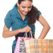 Beautiful young woman looks in the bag for shopping — Stock Photo