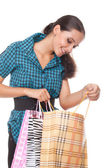 Lovely young woman looks in the bag for shopping — Stock Photo