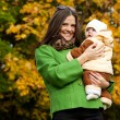 Happy mother holding baby in park — Stock Photo