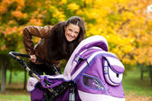 Young mother with baby in stroller walks in park — Stock Photo