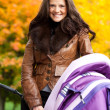 Happy mother with pram — Stock Photo